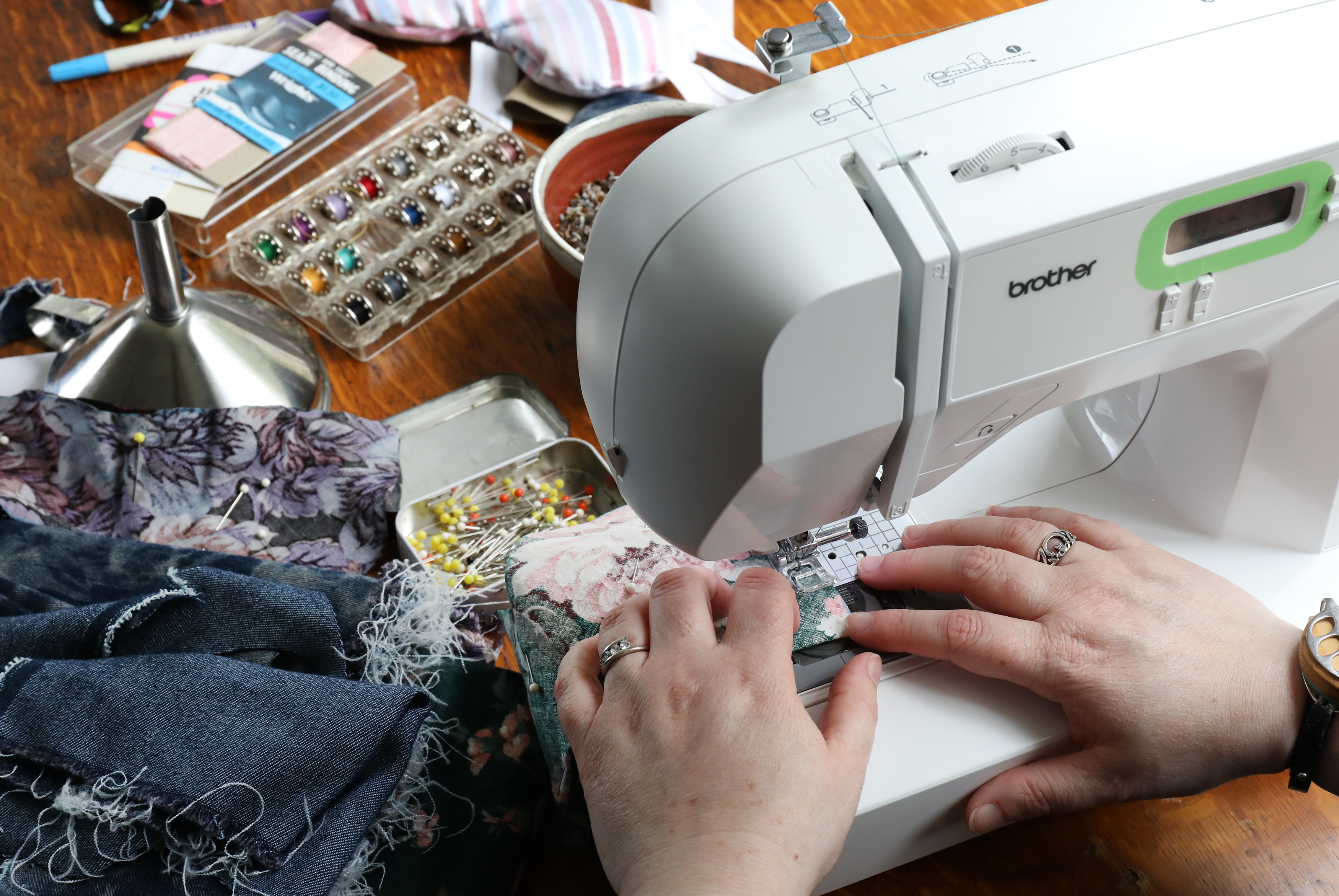 hands on sewing machine sewing fabric to make buckwheat lavender eye pillows