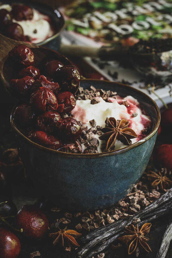 Bowl of yogurt with poached cherries and botanical garnishments