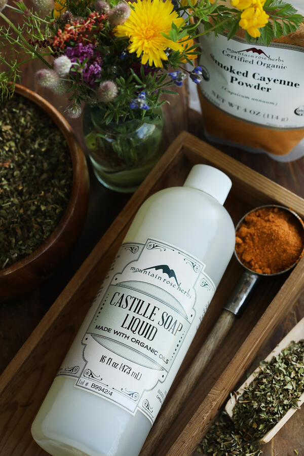 A bottle of castille soap with cayenne powder to make natural pest control garden spray. Colorful bee-friendly flowers in the background.