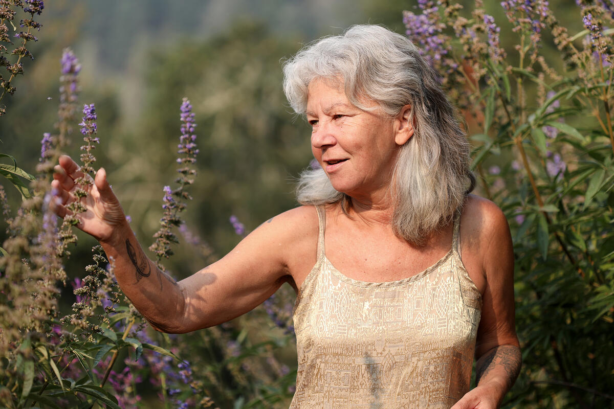 Beautiful gray-haired woman admiring the purple blossoms that are attracting pollinators in her garden
