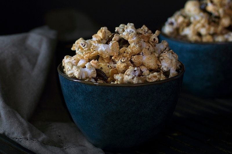 Blue bowl stuffed with caramel popcorn in front of a dark grey background