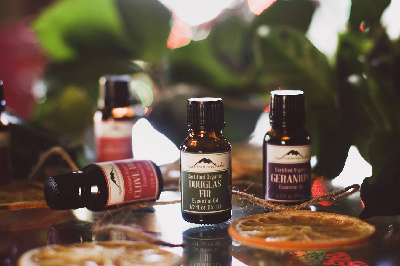 Essential oils on a table with greens ready to blend to make diy potpourri.