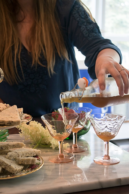 Woman pouring simple syrup into cocktail glasses next to fresh bread and flowers, entertaining