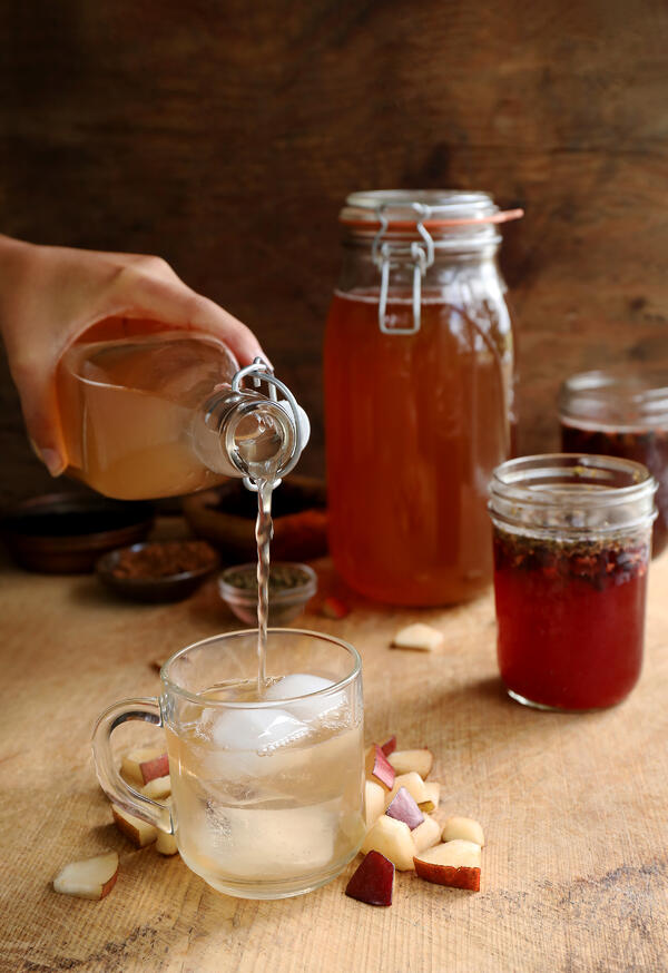 Pouring flavored kombucha into an iced mug. Jars of kombucha are fermenting in the background and fresh pears and herbs add flavor to the beverage.