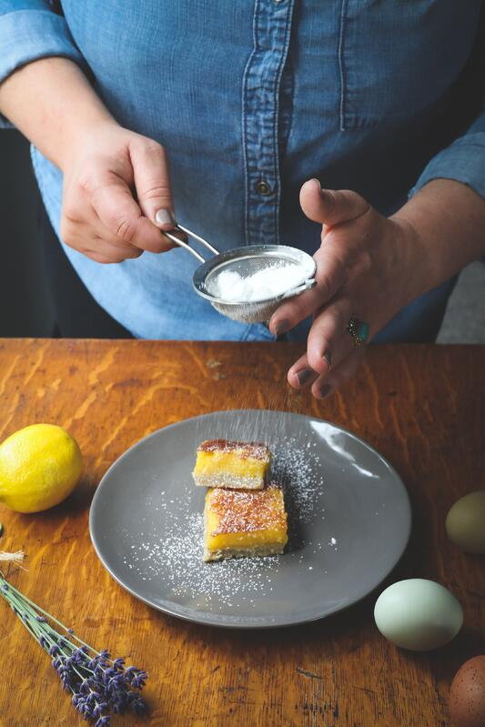 Hands using strainer to dust lemon bars with powdered sugar surrounded with fresh ingredients
