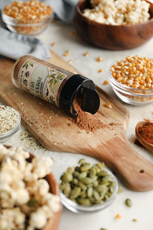 Ingredients for making sweet and spicy popcorn at home. Pumpkin pie spice, popping corn, chipotle powder, pumpkin seeds, and hemp seeds come together for a perfect fall snack.