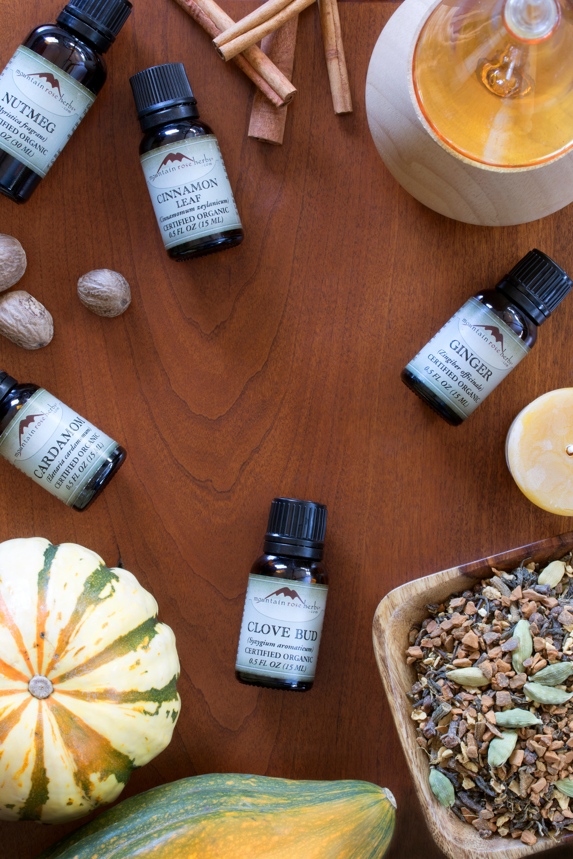 Ginger, Cardamom, and Clove Bud Essential Oils on table with candles, herbs, and pumpkins