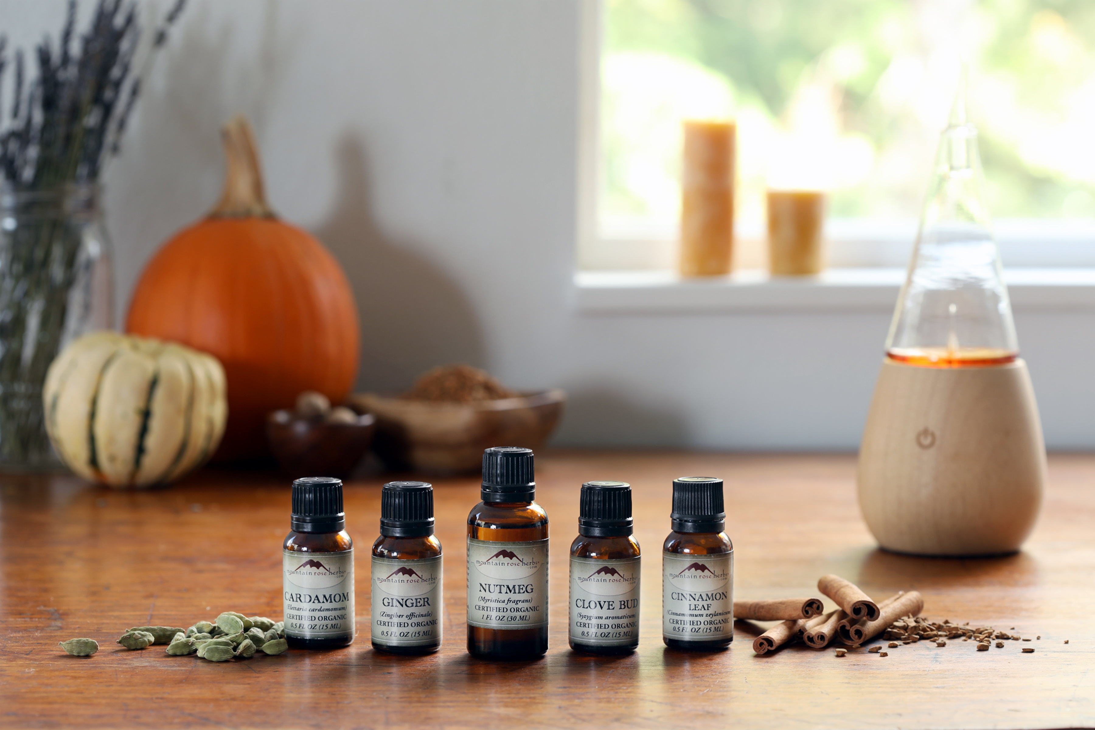 Essential oils, herbs, and diffuser on wooden table with pumpkins