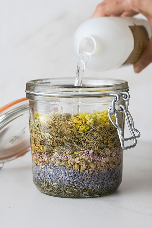 Queen of Hungary's Water dried herbal preparation pantry jar filled with dried herbs and hand pouring extract into jar