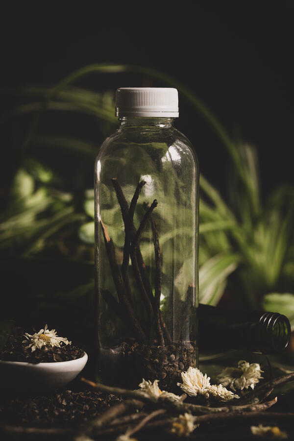 clear glass bottle with sticks inside with plants in the background