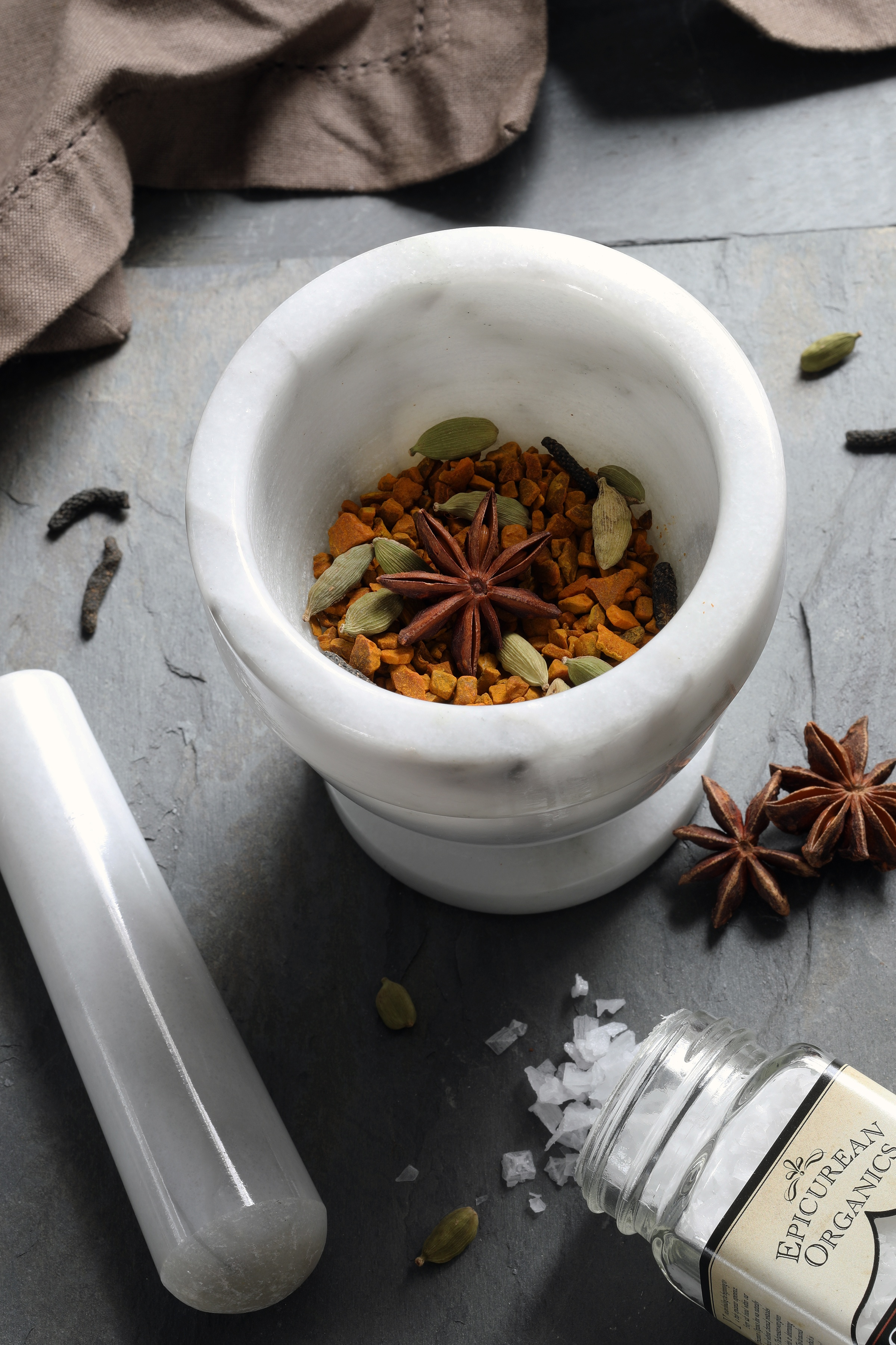Whole cardamom and star anise and dried turmeric in mortar with pestle on counter