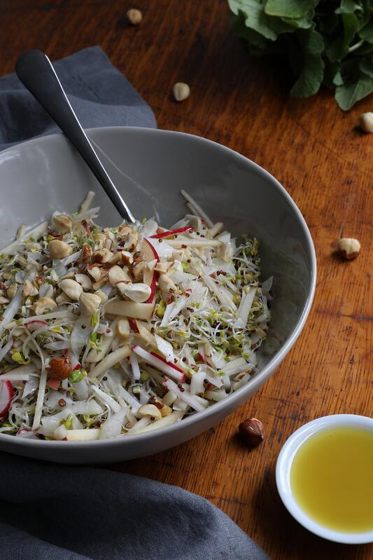 Sprout Salad in a bowl with chopped hazelnuts and radish, with a  serving spoon and fork