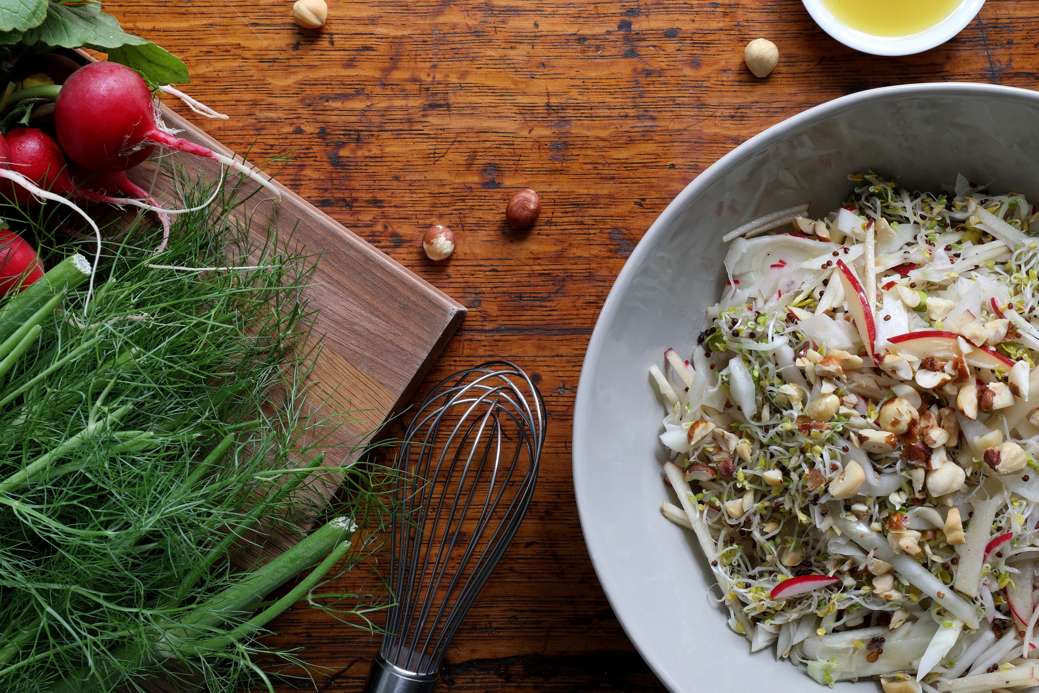 plate of sprout salad on counter top with whisk and radishes and celery
