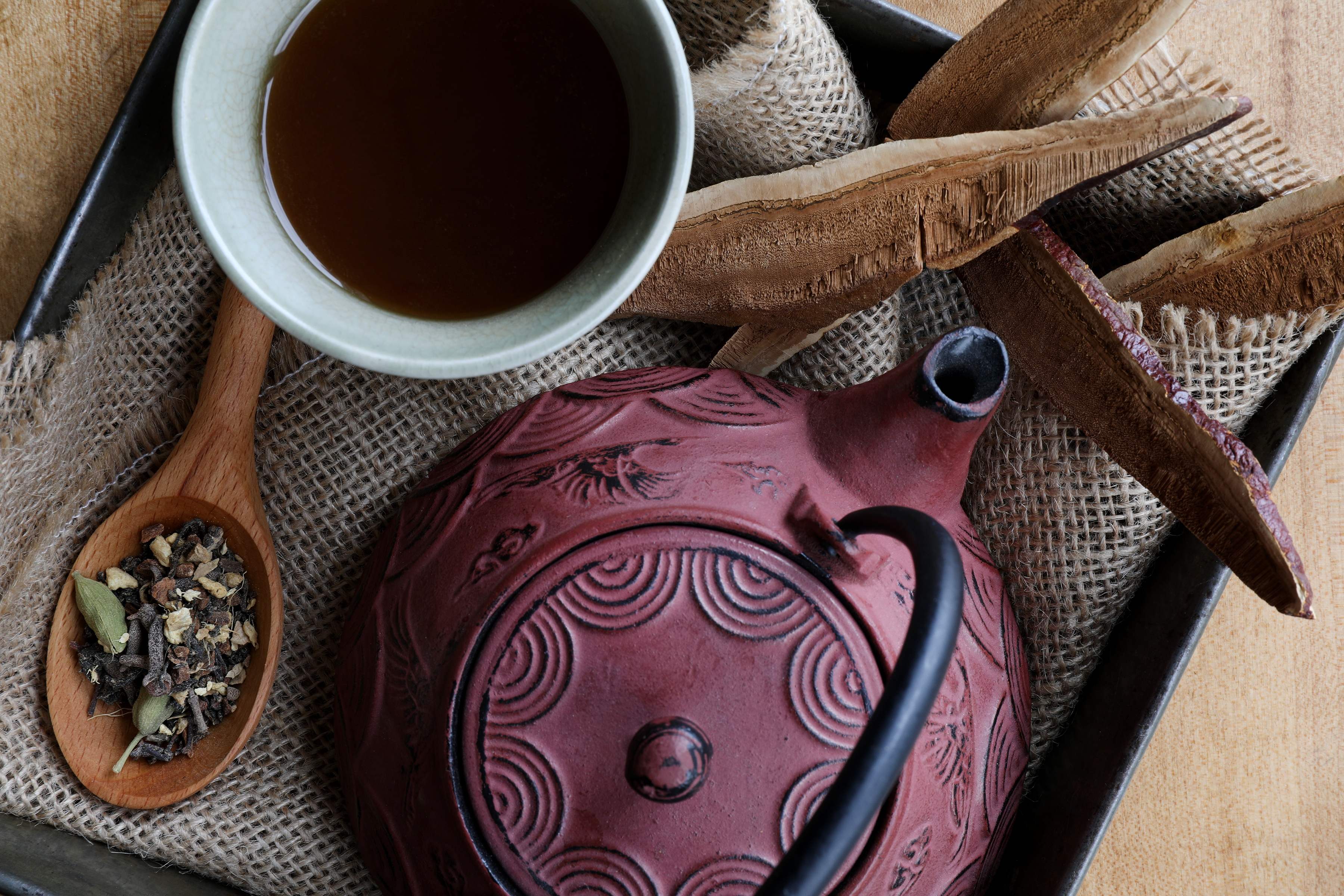 Red cast iron teapot with cup of hot tea, spoon of chai ingredients and Reishi mushroom slices