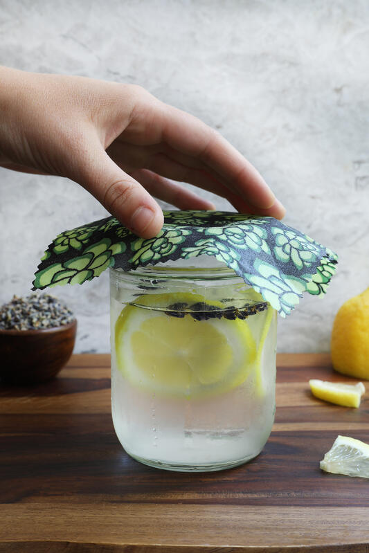 Hand placing colorful beeswax wrap on top of glass of iced water with sliced lemon and botanicals.