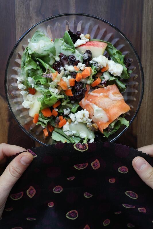 Hands about to cover bowl of colorful salad with a DIY beeswax wrap