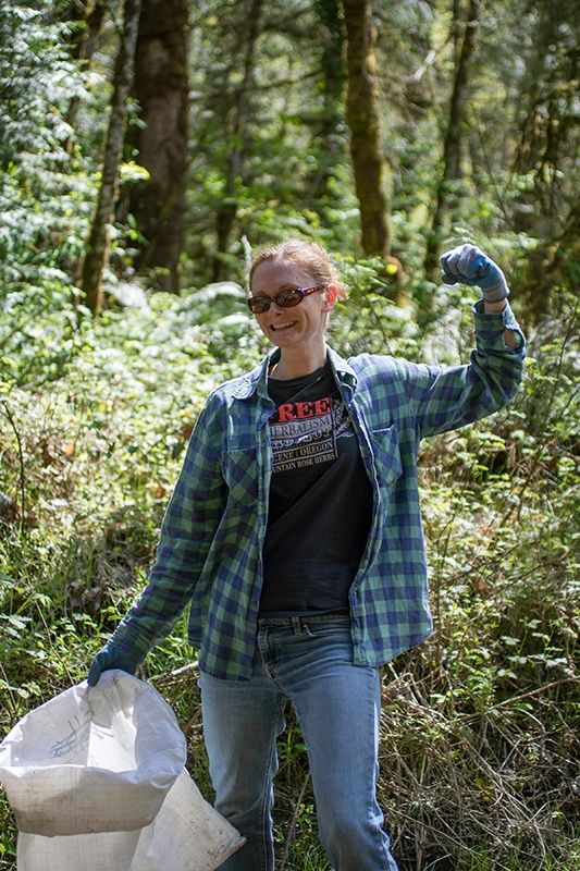 Mountain Rose Herbs staff member in the woods doing river and trash clean up
