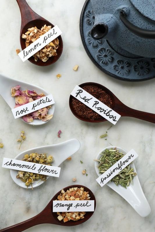 Red rooibos loose leaf tea with spoons of rose petals, chamomile, orange peel and lemon peel