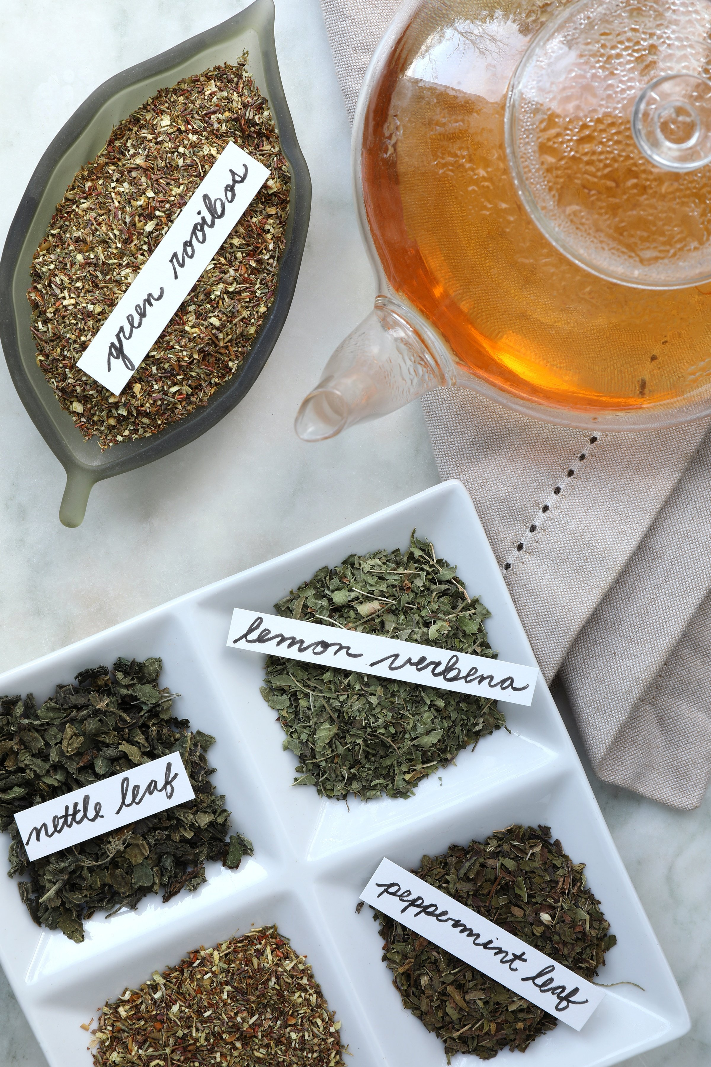 Green rooibos tea with glass tea pot with brewed rooibos tea and herbs nearby