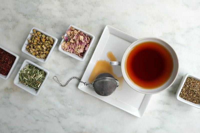 Rooibos Tea in TeaCup with mesh ball tea infuser and ceramic jars of bulk herbs