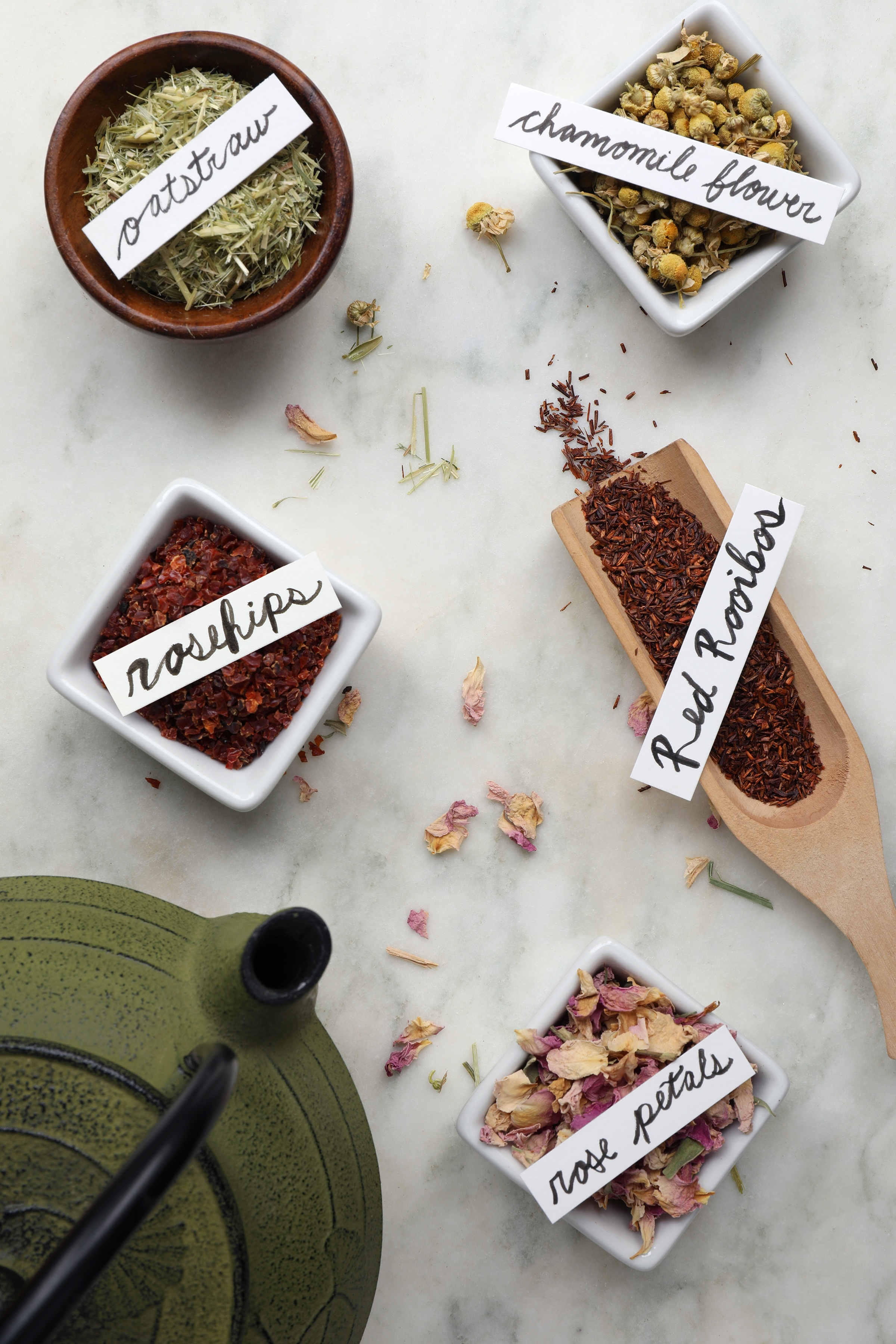 Red Rooibos tea loose-leaf in mini herb shovel near cast iron tea pot and containers of bulk herbs