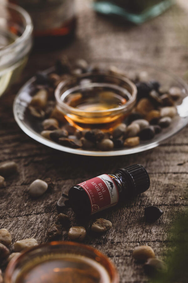 Bottle of rose essential oil in warm setting with small stones