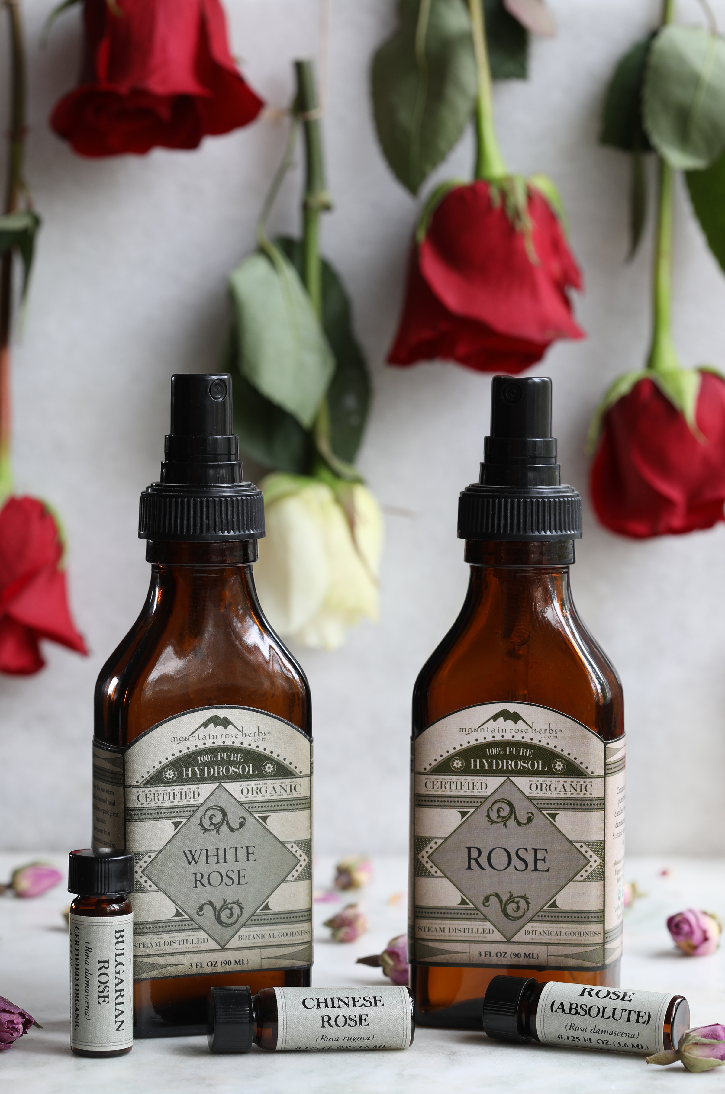 White rose hydrosol, rose hydrosol, and various rose essential oils laying out on counter with rose petals
