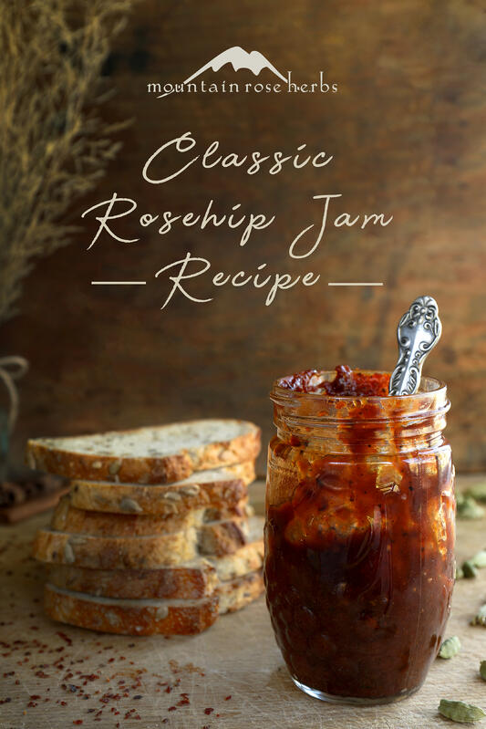 Pinterest link to Mountain Rose Herbs. A jar of homemade rosehip jam using dried rosehips and other ingredients. Toasted whole grain bread and a cheese and fruit board with orange juice in the background.