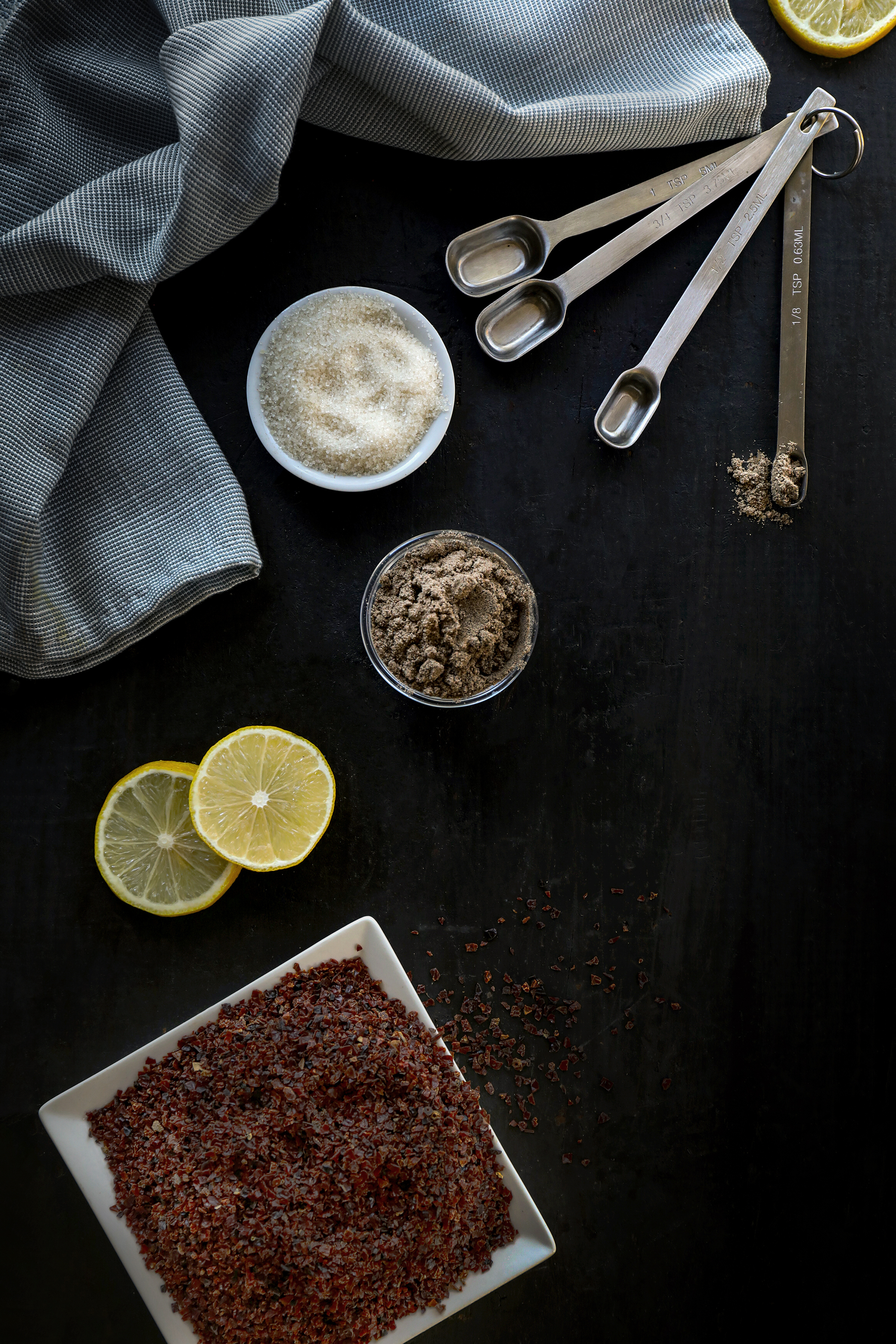 Ingredients for a freezer jam made with dried organic rosehips, fresh lemon, organic cardamom powder, and cane sugar.
