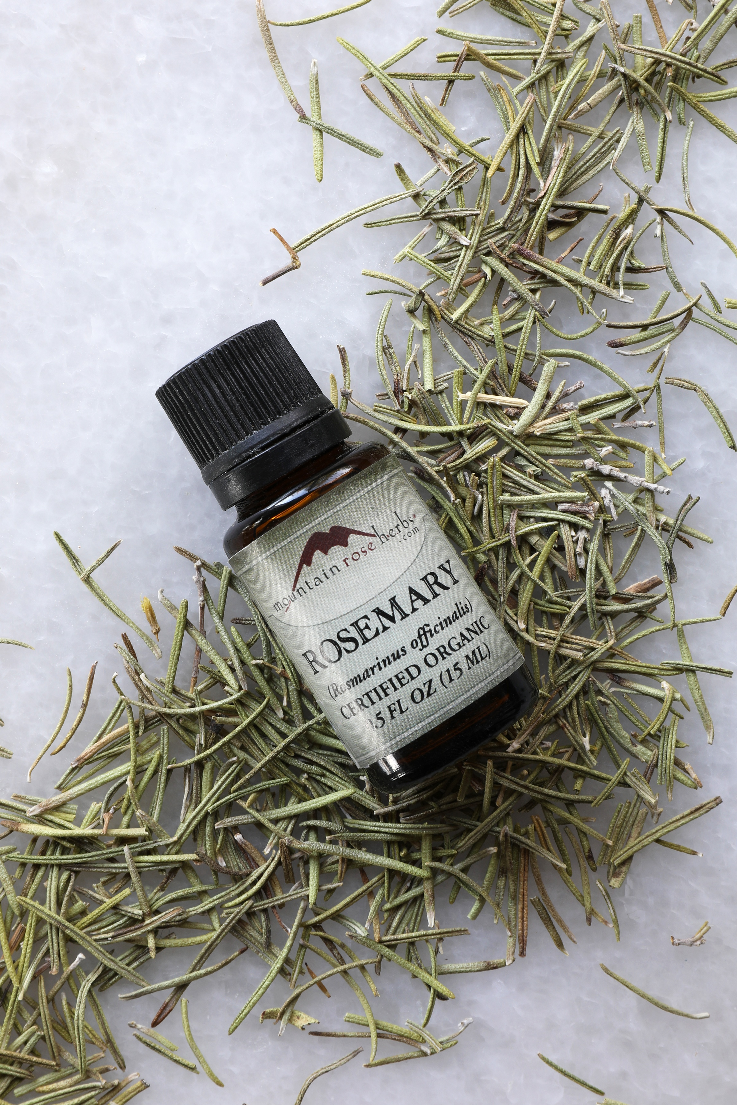 1/2 oz. bottle of rosemary essential oil laying on rosemary leaves