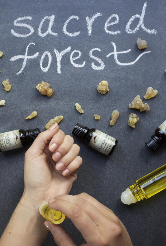 Person using roll on to apply perfume oil to wrists with essential oil bottles artfully displayed around.