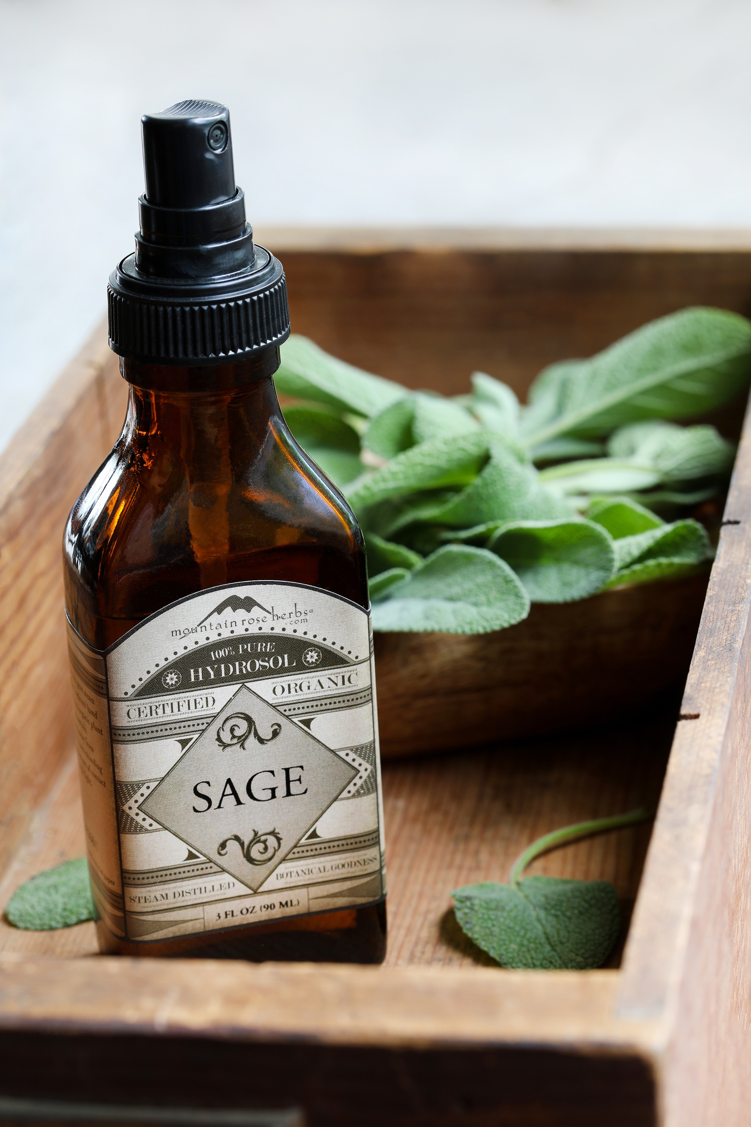 Amber mister bottle of organic sage hydrosol in shallow wooden crate with fresh sage leaves