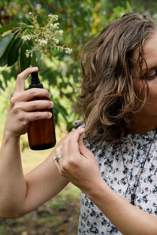 A woman applying rosemary salt spray to her hair while outdoors. Wearing a white floral shirt, a woman sprays from a dark amber bottle onto her short brown hair.