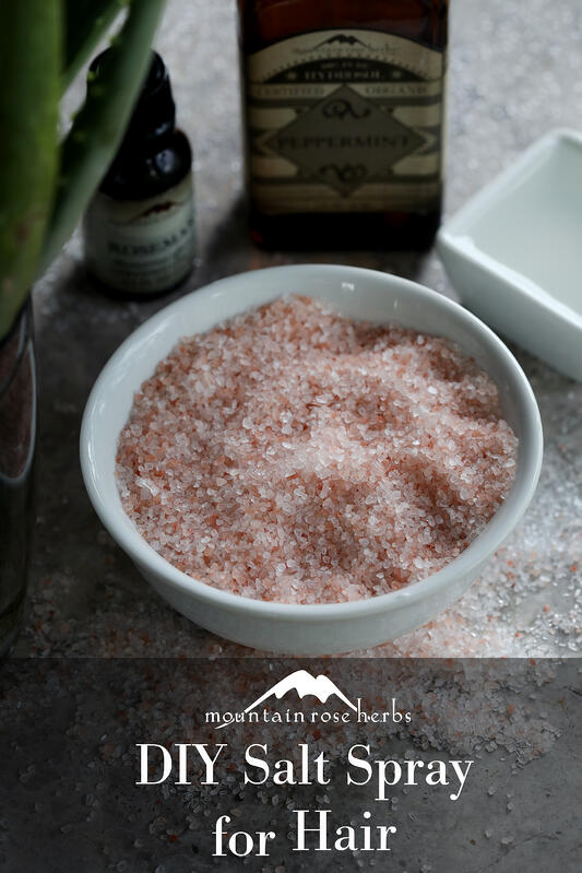 Pinterest link to Mountain Rose Herbs. A bowl of course Himalayan pink salt, aloe vera, essential oils, and hydrosols all arranged on a gray background.