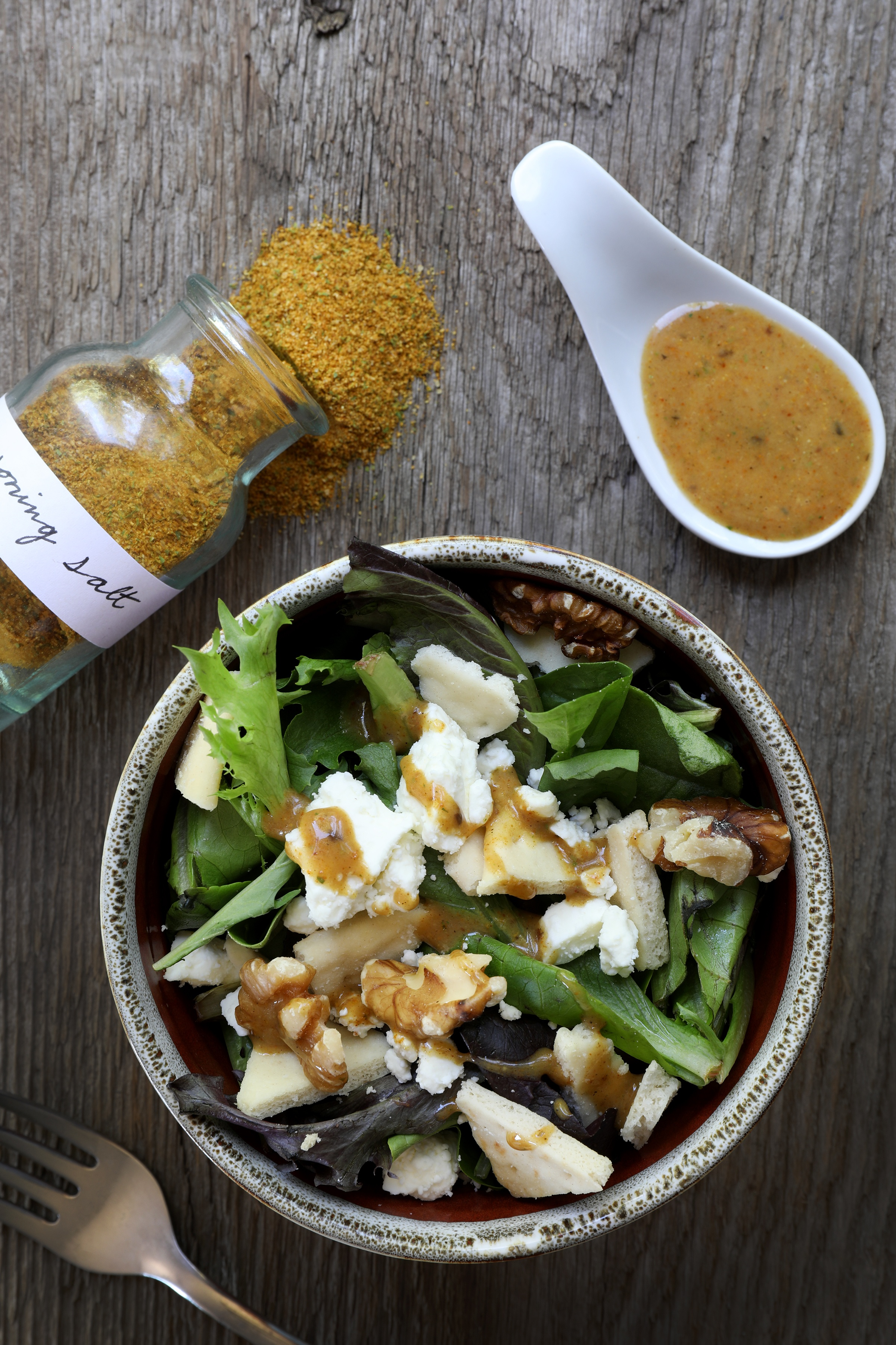 Bowl of salad with bottle of seasoning salt and salad dressing on spoon