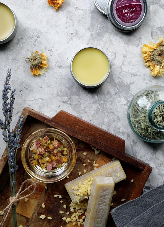Dream balm salve sitting on counter with beeswax and other salve ingredients