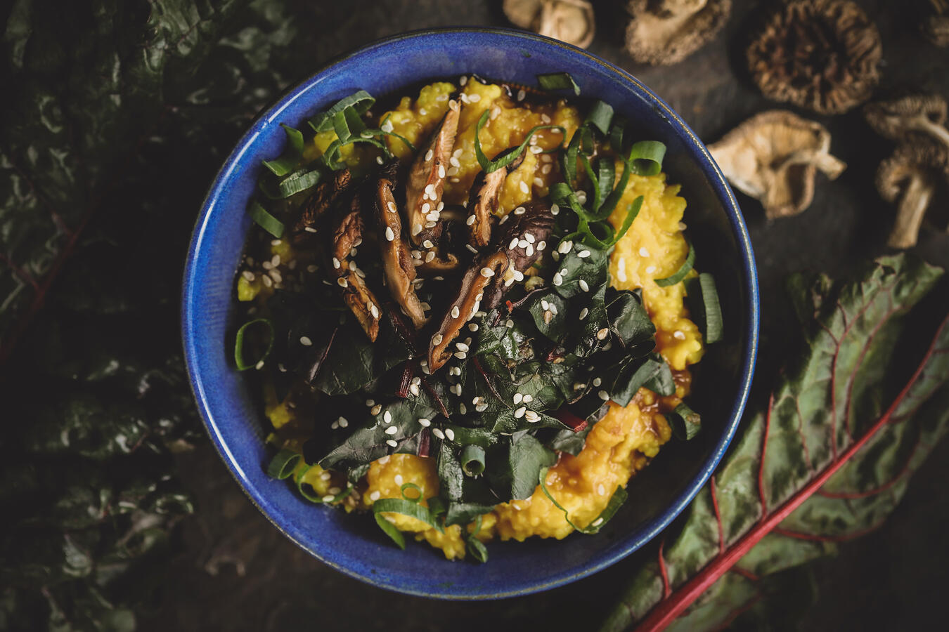 Golden congee in a vibrant blue bowl with sliced mushrooms and greens- garnished with sesame seeds.