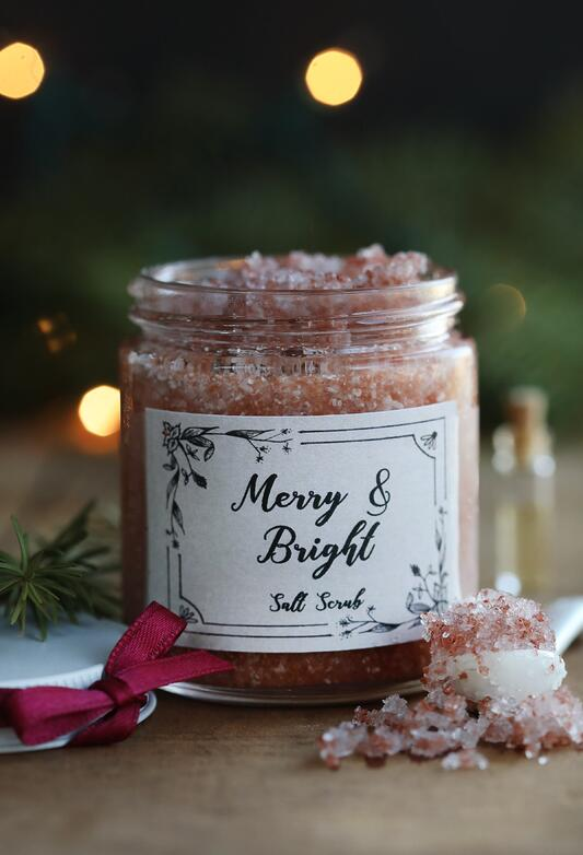 Glass jar filled with pink bath salts with words Merry and Bright Salt Scrub with homemade label