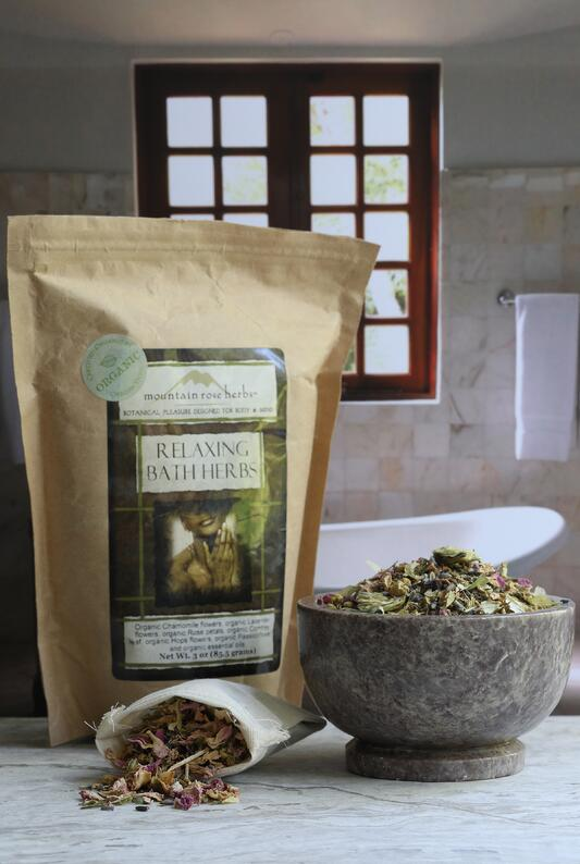 Paper bag and mortar and muslin bag filled with relaxing bath herbs sitting on counter outside of tub