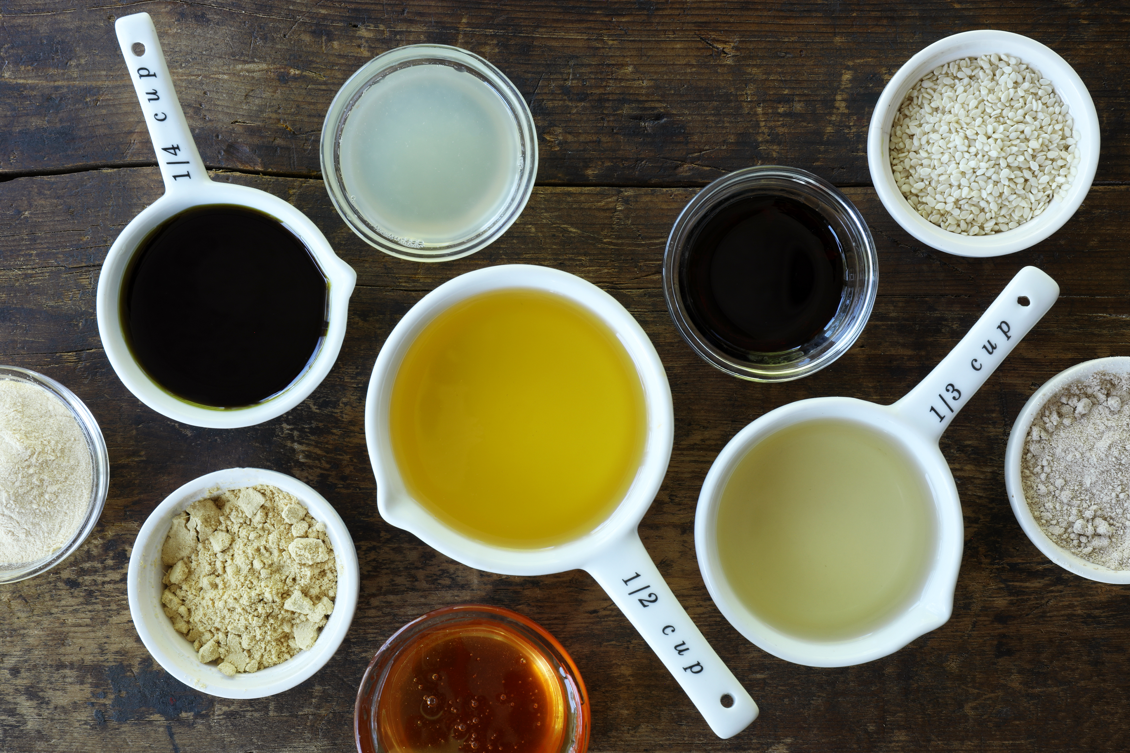 Measuring cups and bowls of oils and spices for Asian salad dressing arrayed on wooden table.