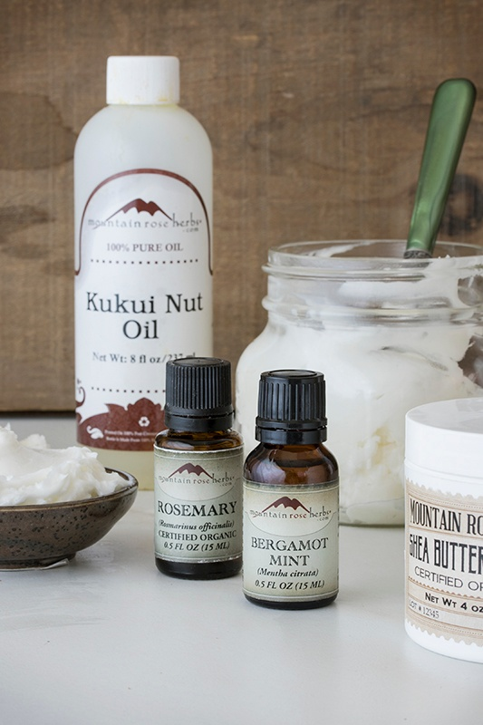 .5 oz bottles of bergamot mint essential oil and organic rosemary essential oil sitting on a counter with shea butter and kukui nut oil for recipe making