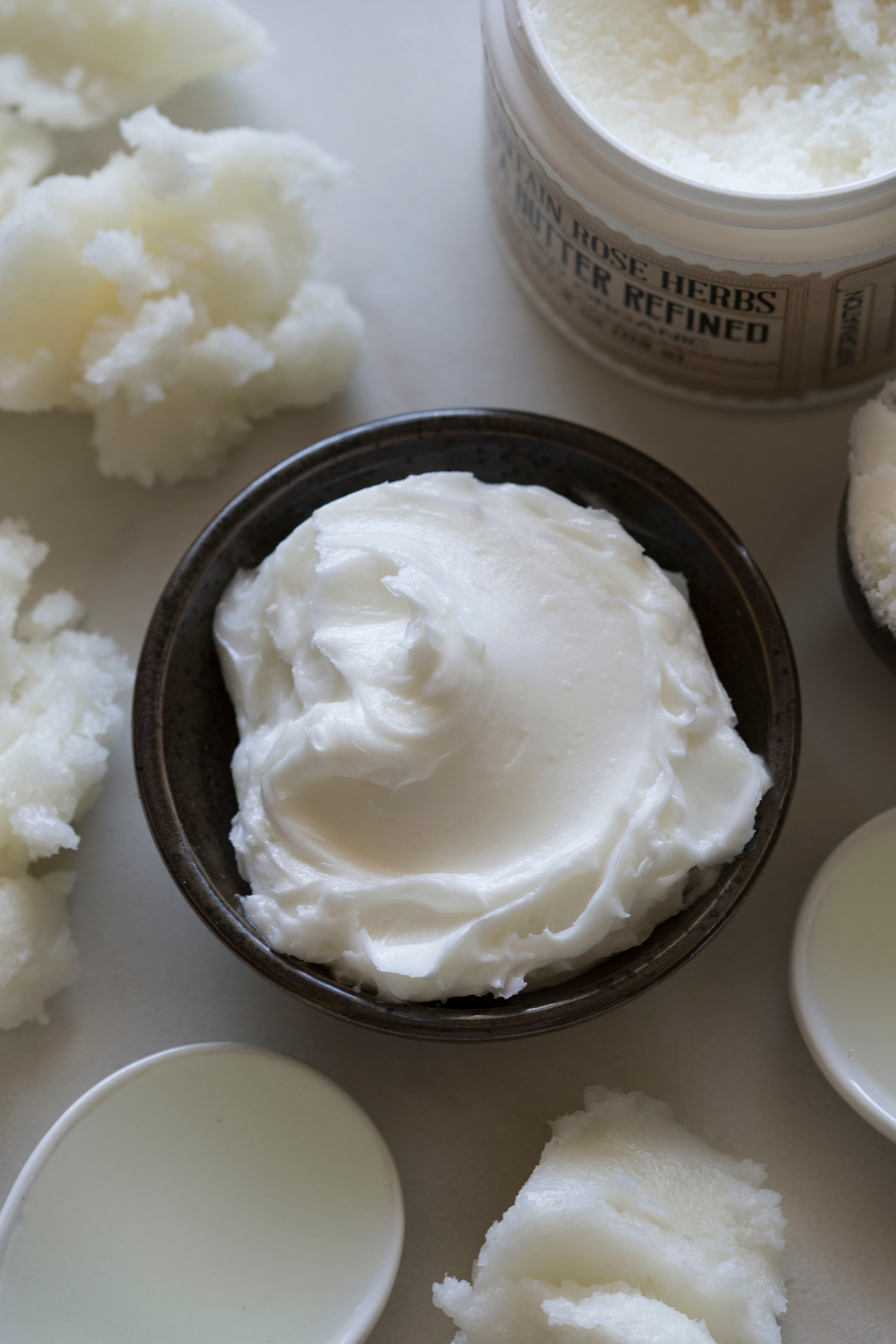 Bowl of homemade whipped shaving cream on counter with organic butters and ingredients