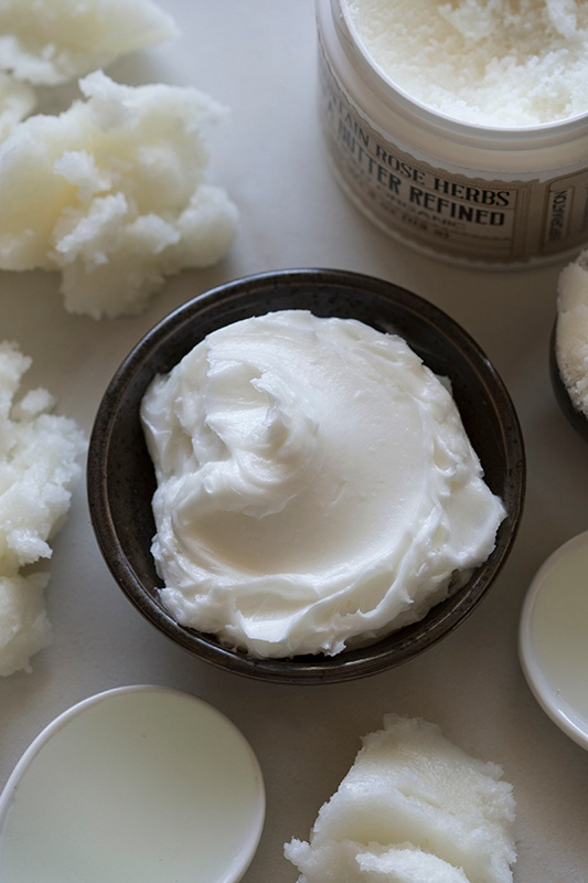Bowl of whipped shaving cream sitting on counter next to shea butter and kukui nut oil
