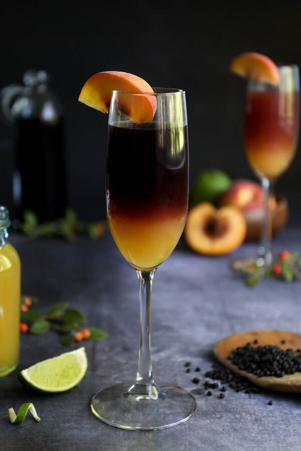A two-tone elderberry peach Bellini in a champagne flute, topped by a slice of peach