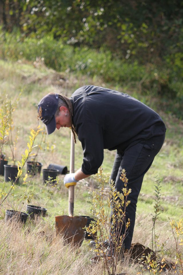 Shawn Donnille volunteering in a field, planting small trees and leaning over a shovel
