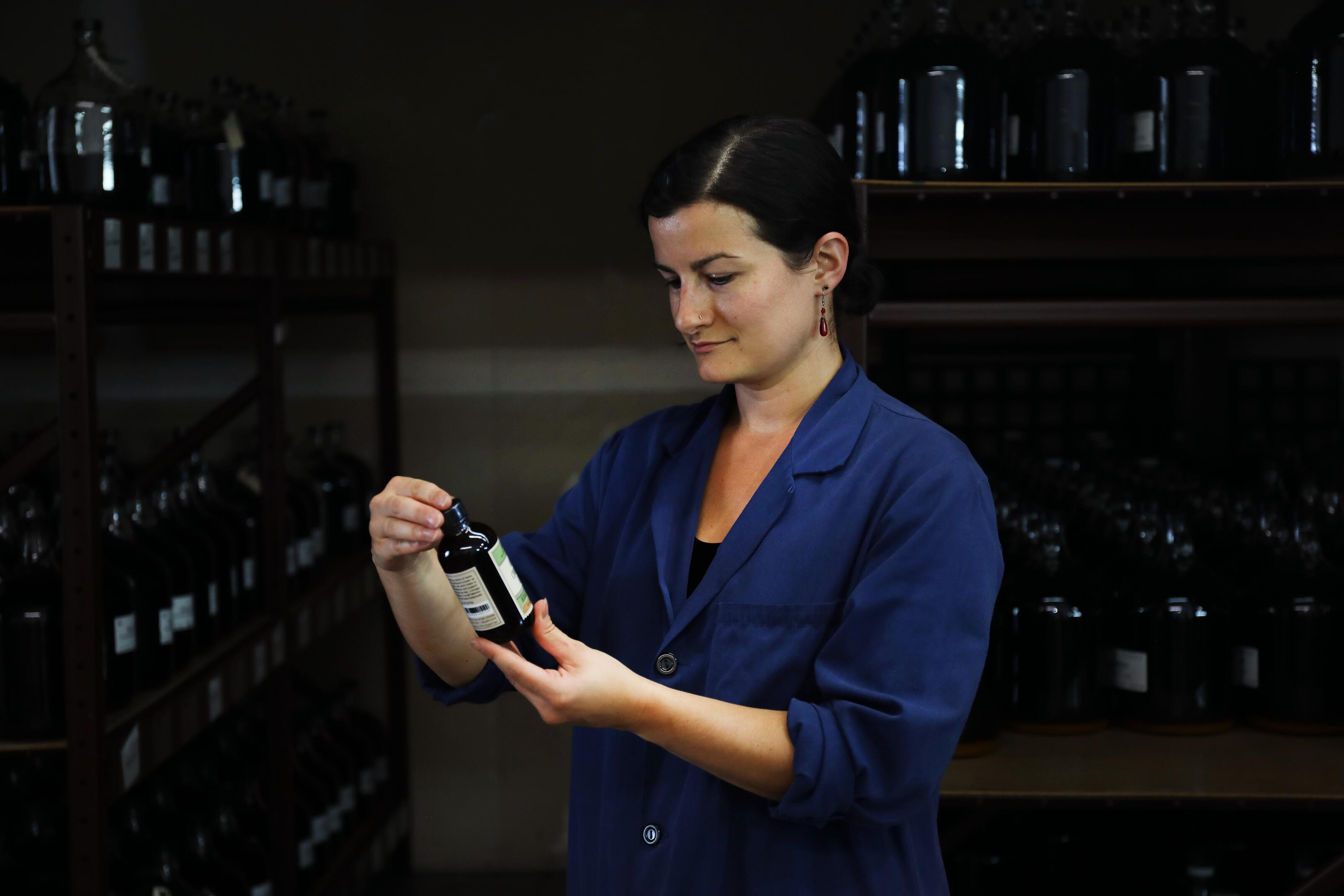 Shay inspects a completed bottle of elderberry syrup. She is in a room filled with shelves of large glass jars holding various herbal mixtures.
