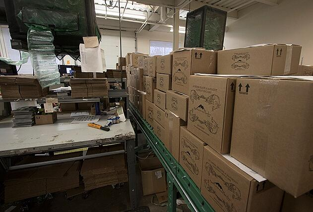 Piles of Mountain Rose Herbs recyclable shipping boxes next to shipping station where people ship orders