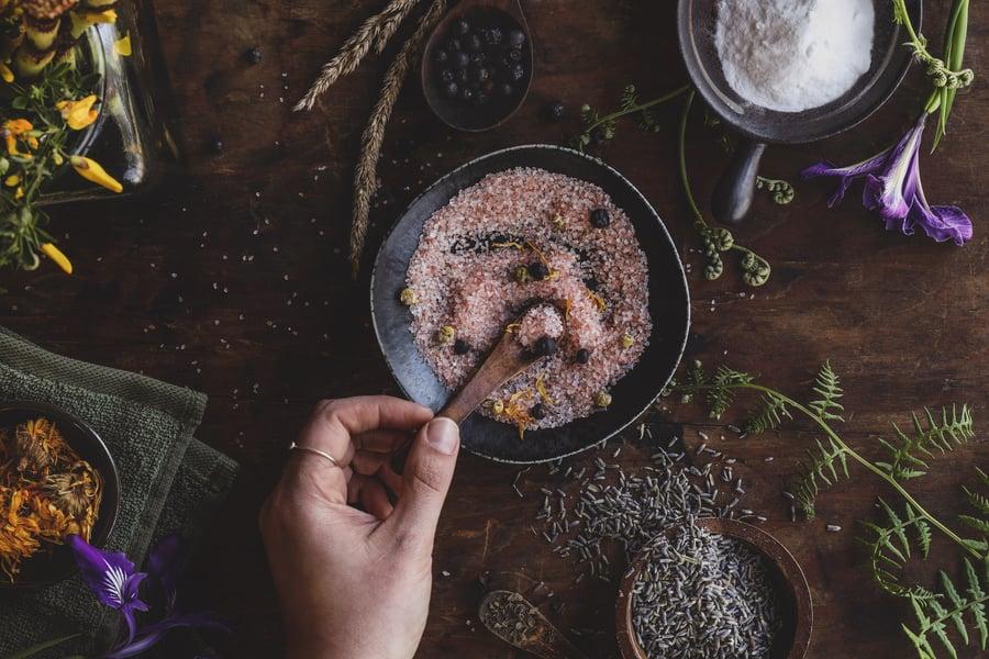 A person mixing lavender into bath salts for an herbal sitz bath.