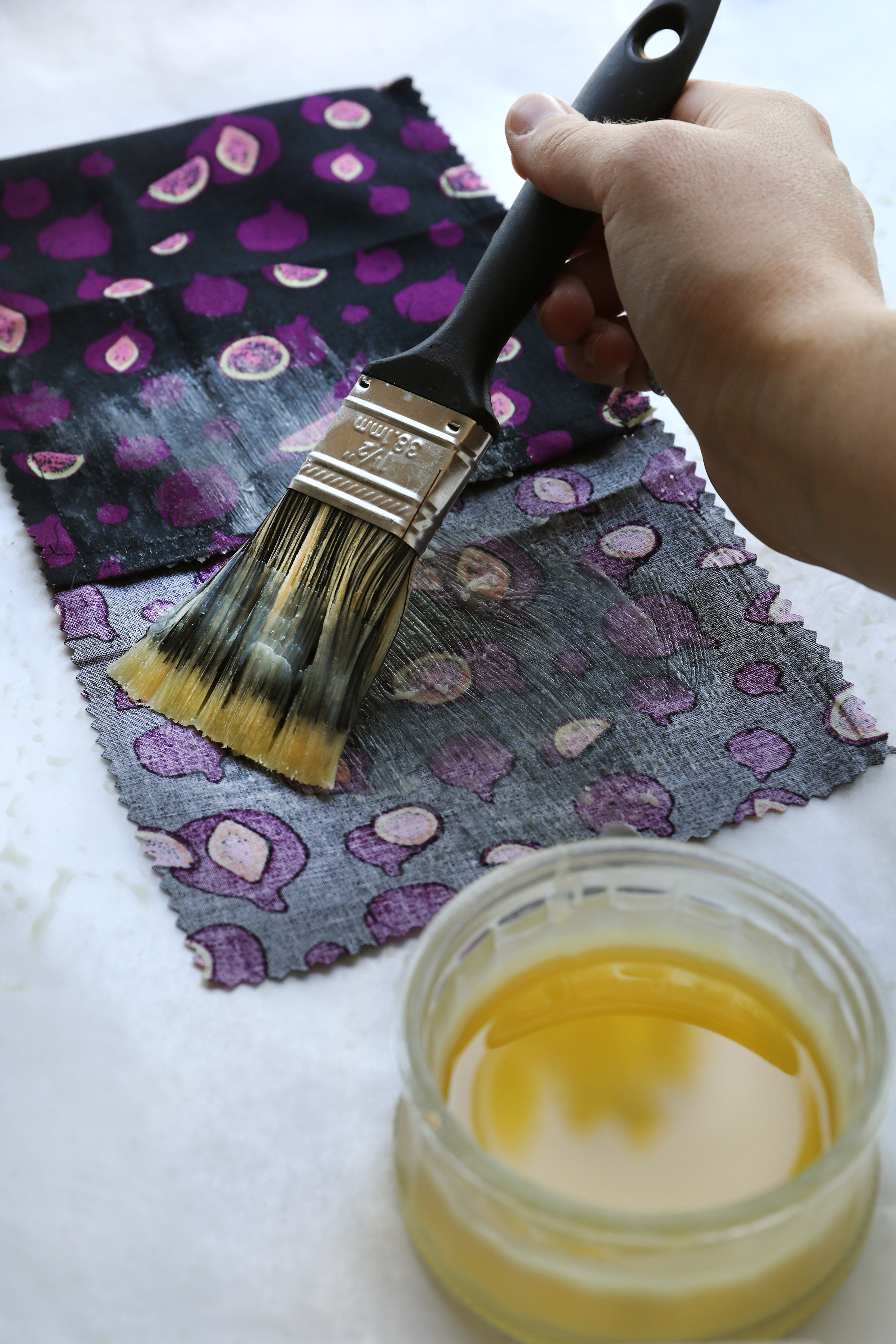 Hand with brush applying golden substance to decorative cloth for DIY food wrap