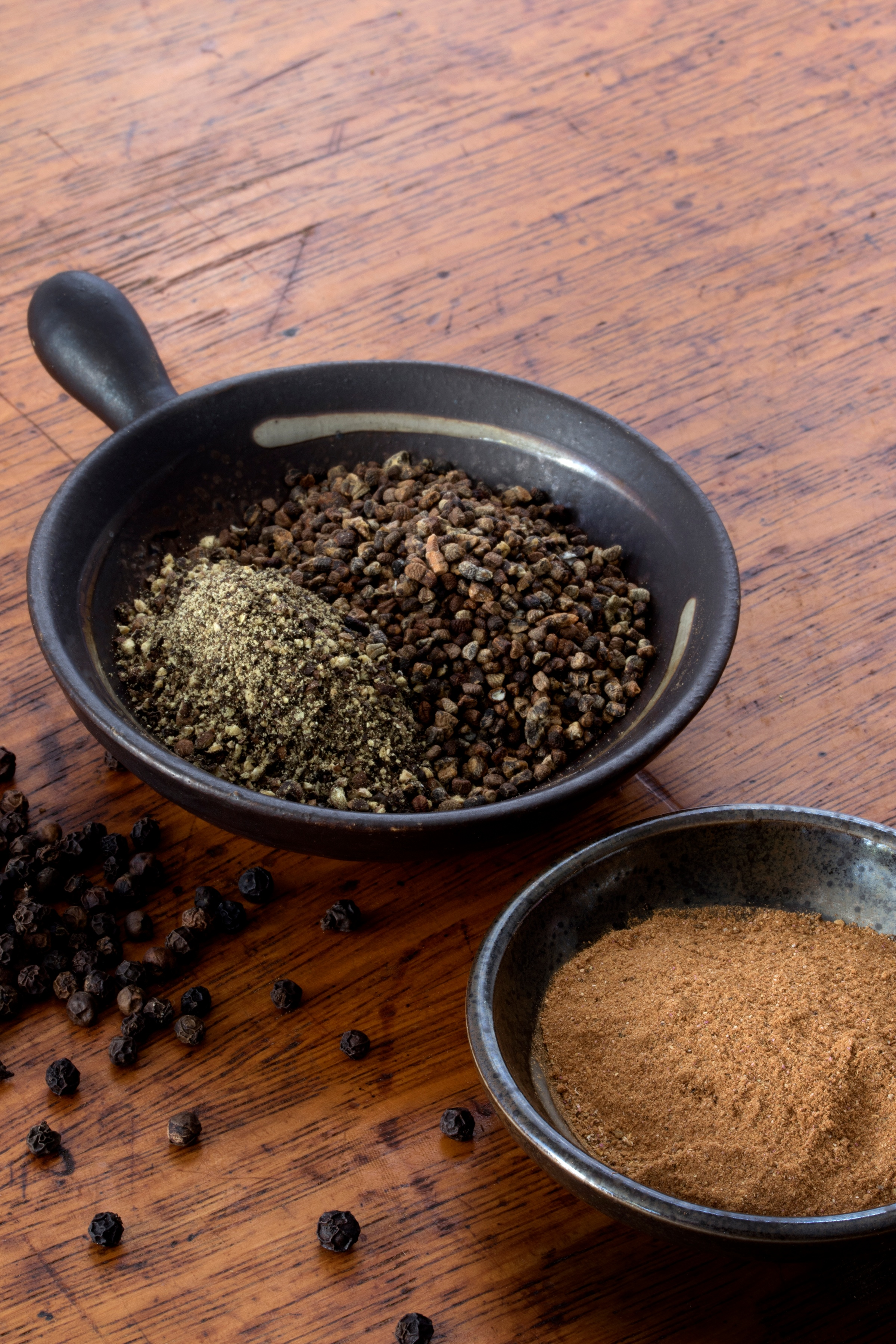 Hulled cardamom, black pepper and peppercorns, cinnamon powder and other spices in bowls on wooden table